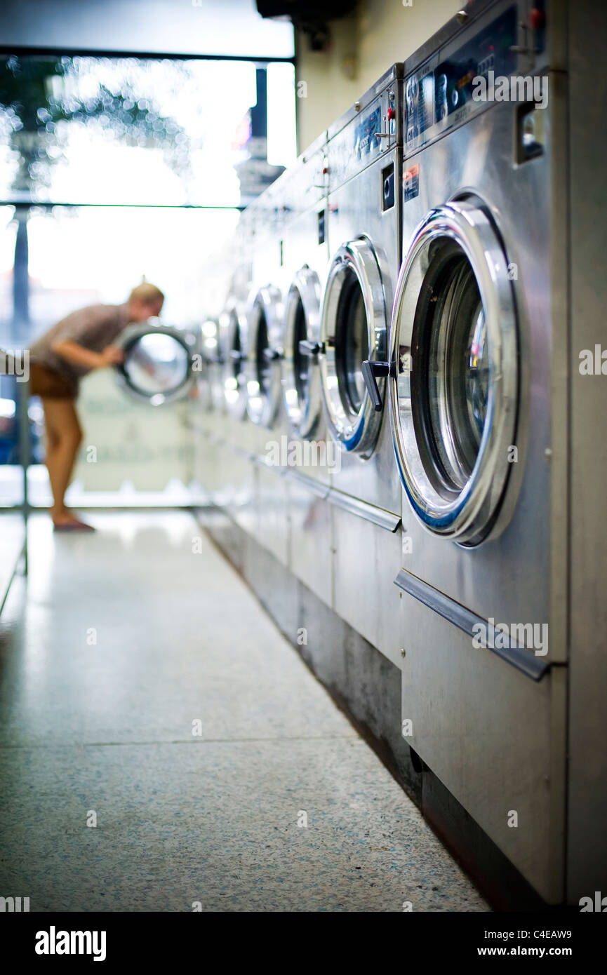 Young woman in laundromat - Stock Image