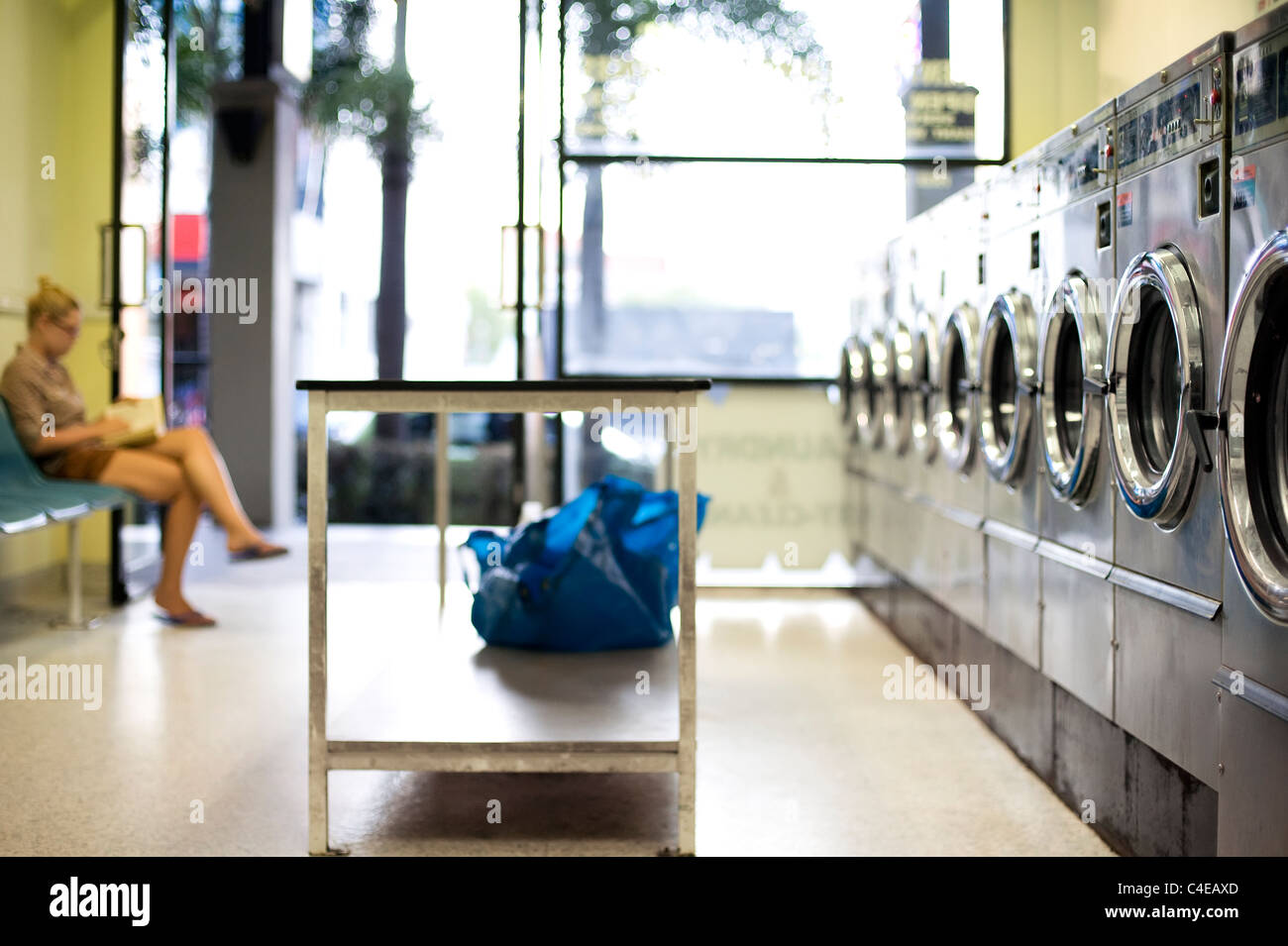 Girl waiting for washing in laundromat - Stock Image