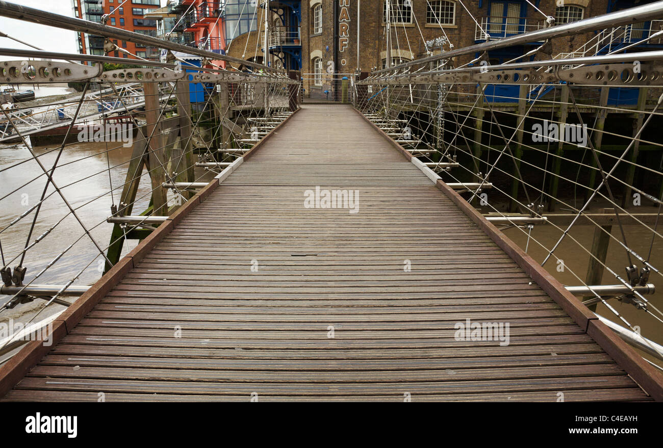An old iron bridge entrance to St. Savior's Dock, Shad Thames, London. - Stock Image
