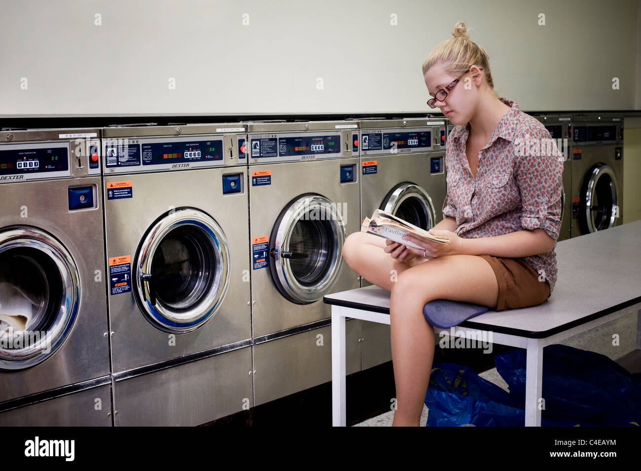 Girl reading book at laundromat - Stock Image