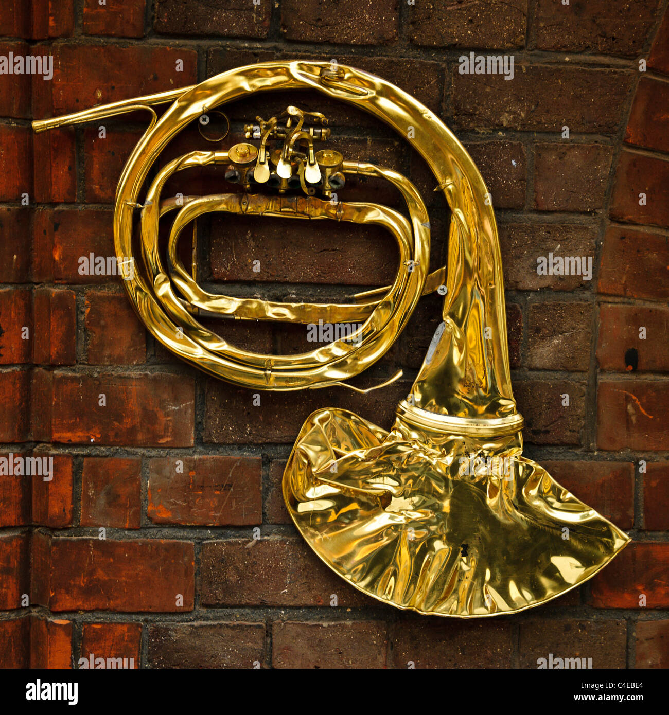 A flattened French Horn hanging on the walls at AIR Lyndhurst Studios, London - Stock Image