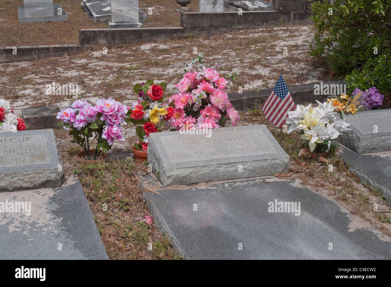 Artificial flowers and American flag mark the gravesites in Carrabelle cemetery along Florida's Gulf coast. - Stock Image