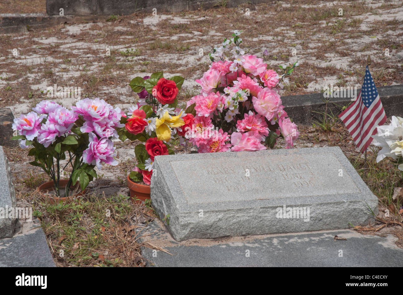Artificial Flowers And American Flag Mark The Gravesites In Stock