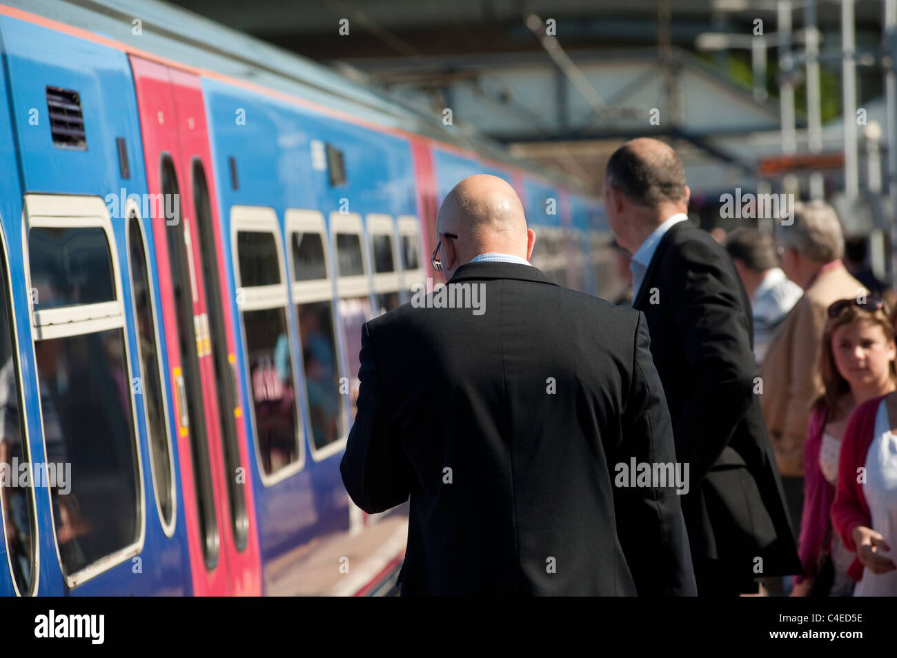 Passengers standing on a railway station platform waiting to board a First Capital Connect train in England. - Stock Image