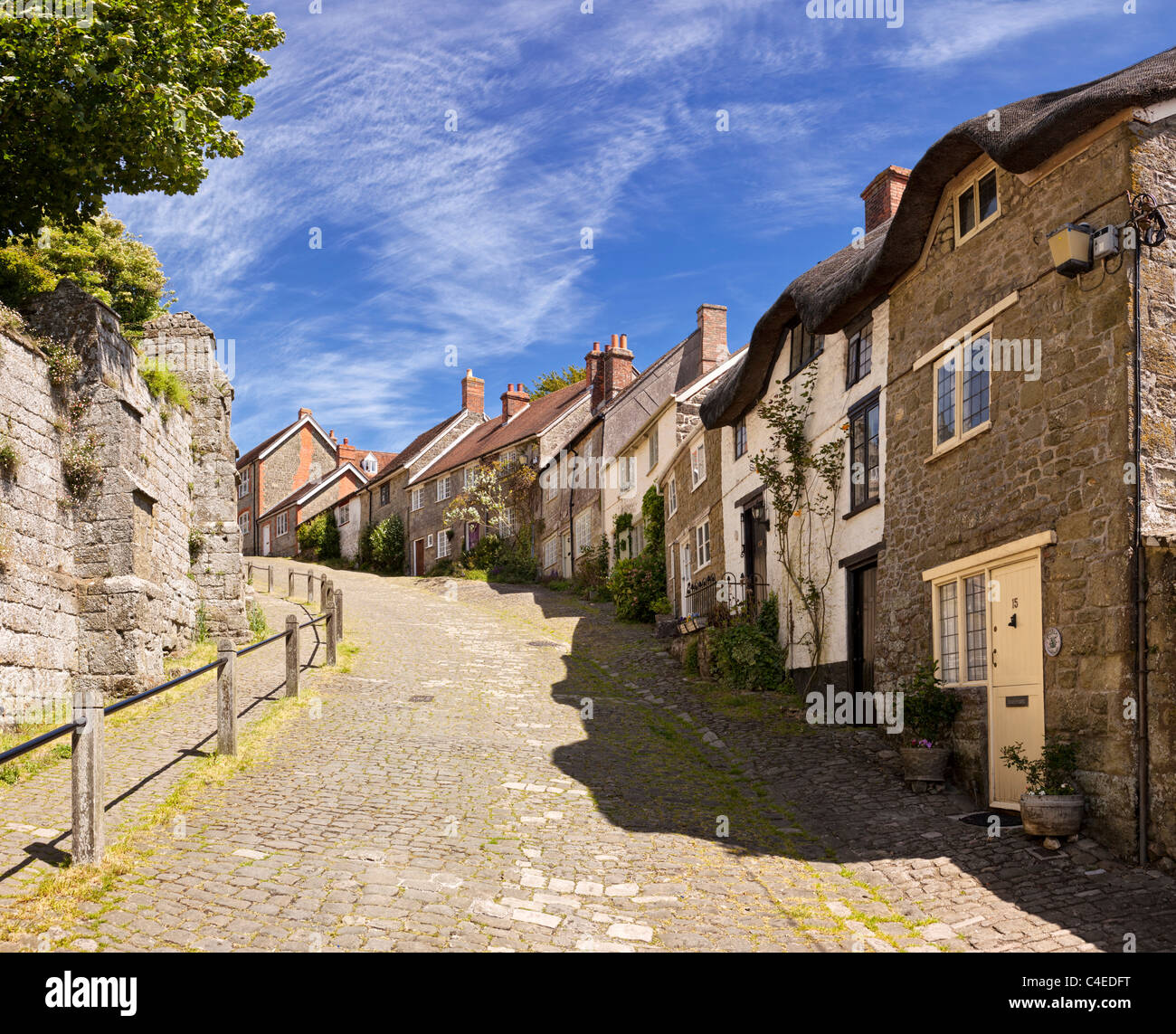 Typical traditional English cobbled street on Gold Hill, Shaftesbury, Dorset, England, UK viewed from bottom of - Stock Image