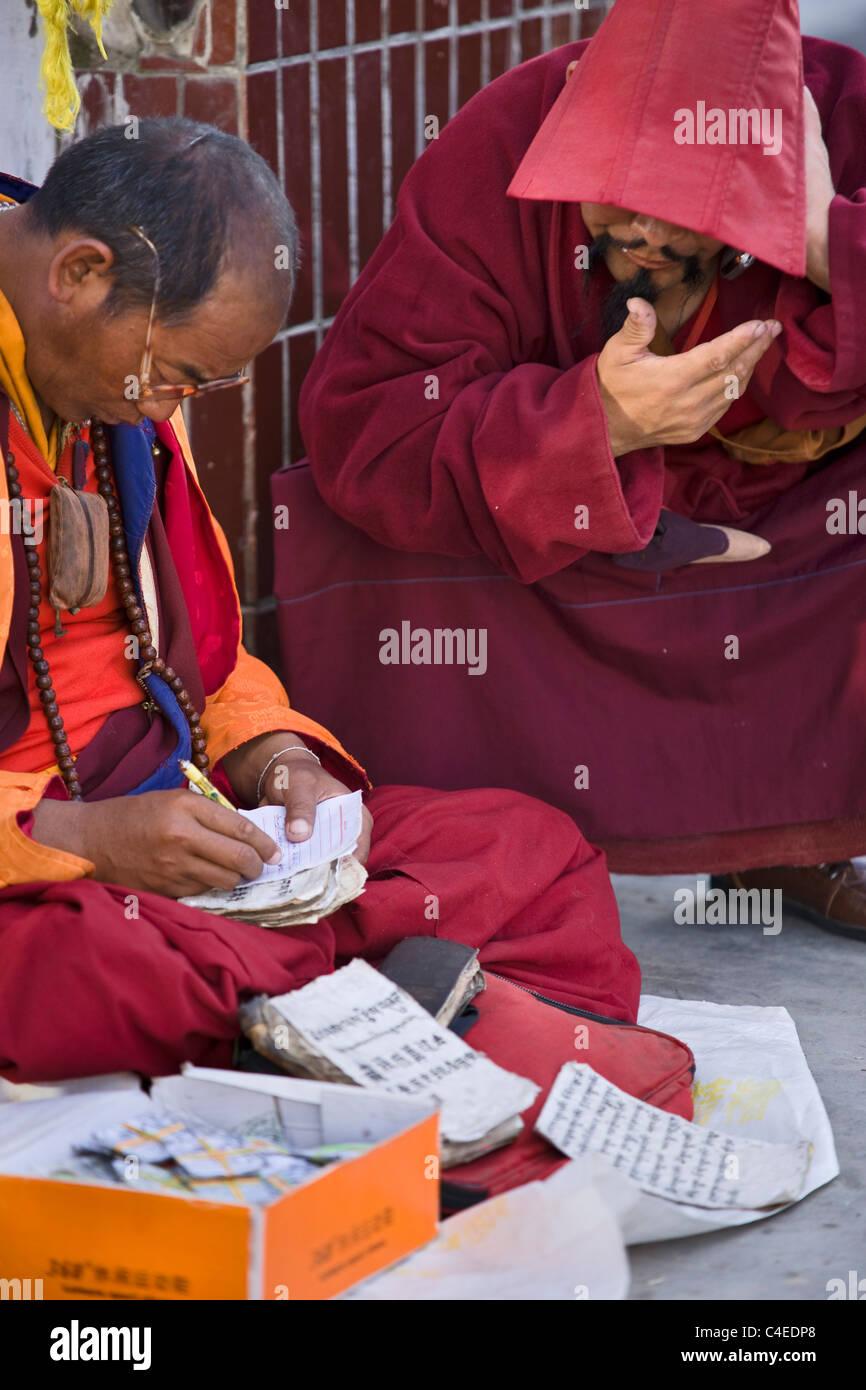 Fortune teller and Tibetan monk, Ganzi, Sichuan, China - Stock Image