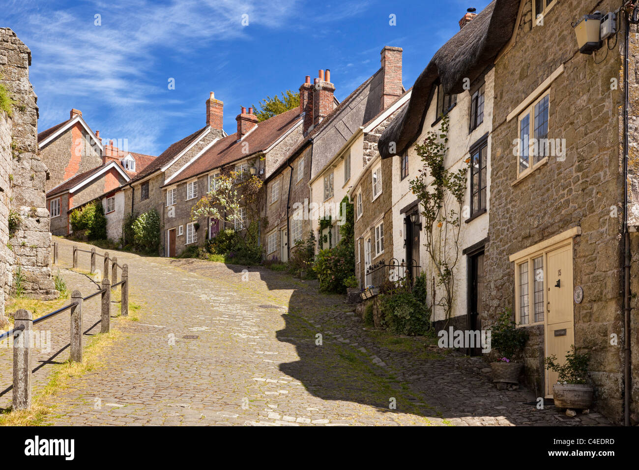 Traditional English houses on Gold Hill, Shaftesbury, Dorset, England, UK viewed from bottom of street - Stock Image