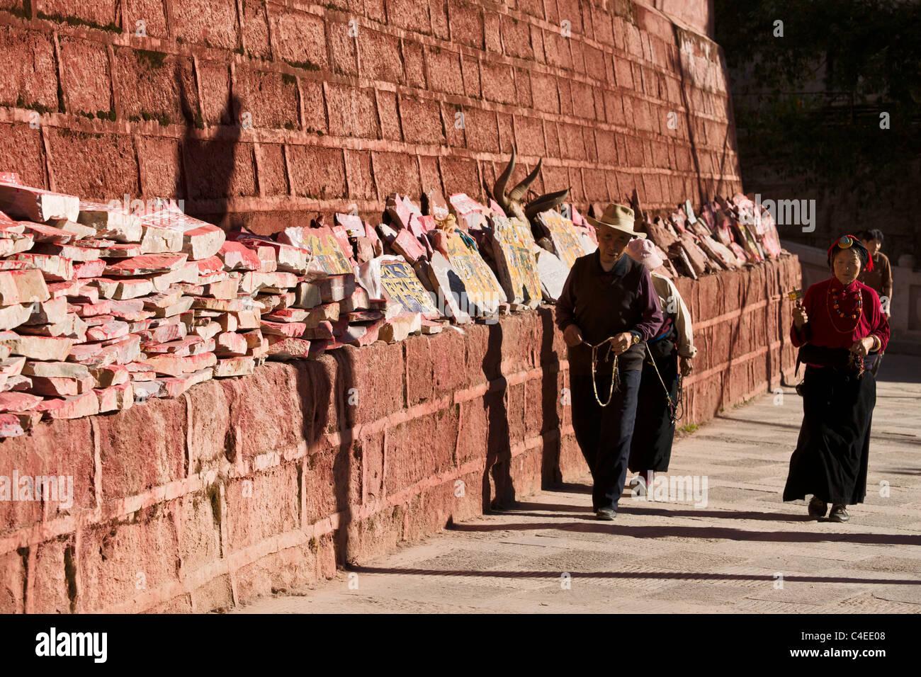 Tibetan pilgrims circumnambulating around Dege Scripture Printing House, Dege, Sichuan, China - Stock Image