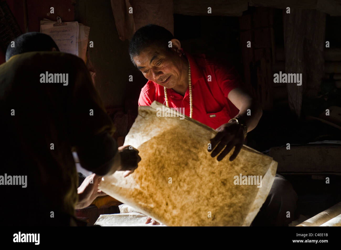 Checking paper quality at Dege Scripture Printing House, Dege, Sichuan, China - - Stock Image