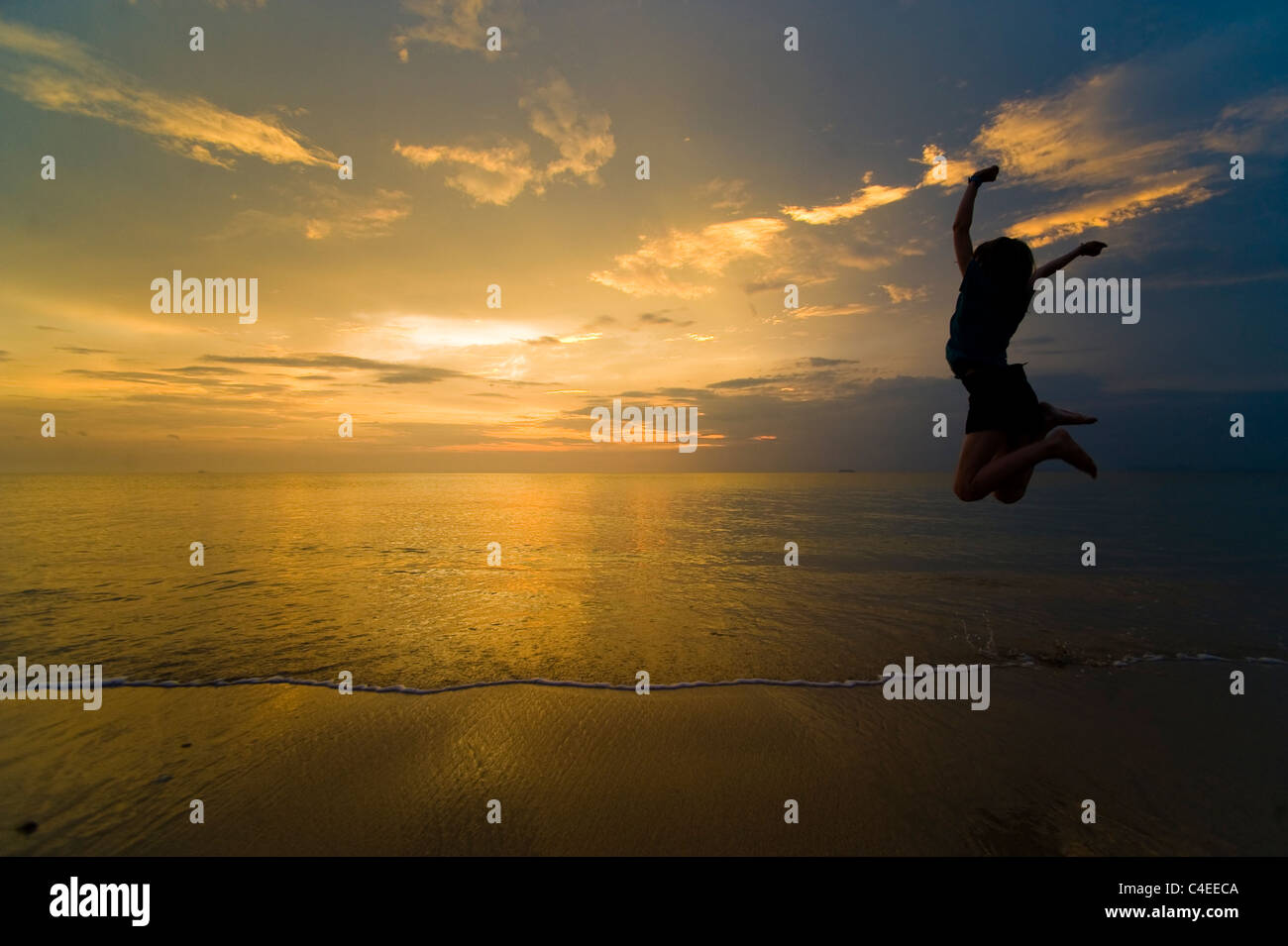 A young woman enjoying her freedom and jumping for joy on the beach at sunset. Taken on Phra Ae Beach, Koh Lanta, - Stock Image