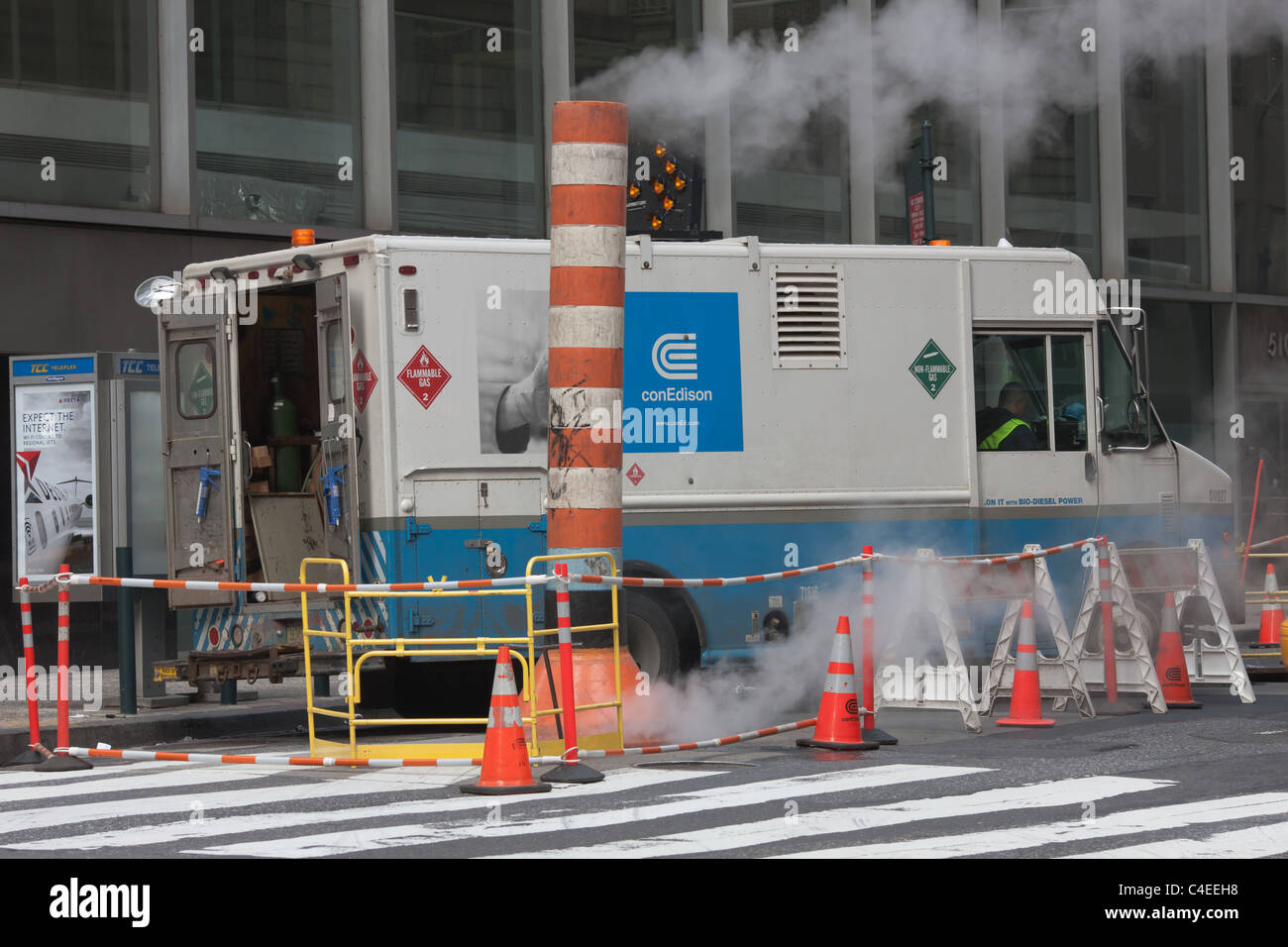 A Con Edison service truck and maintenance crew work at a site on a street in New York City. - Stock Image