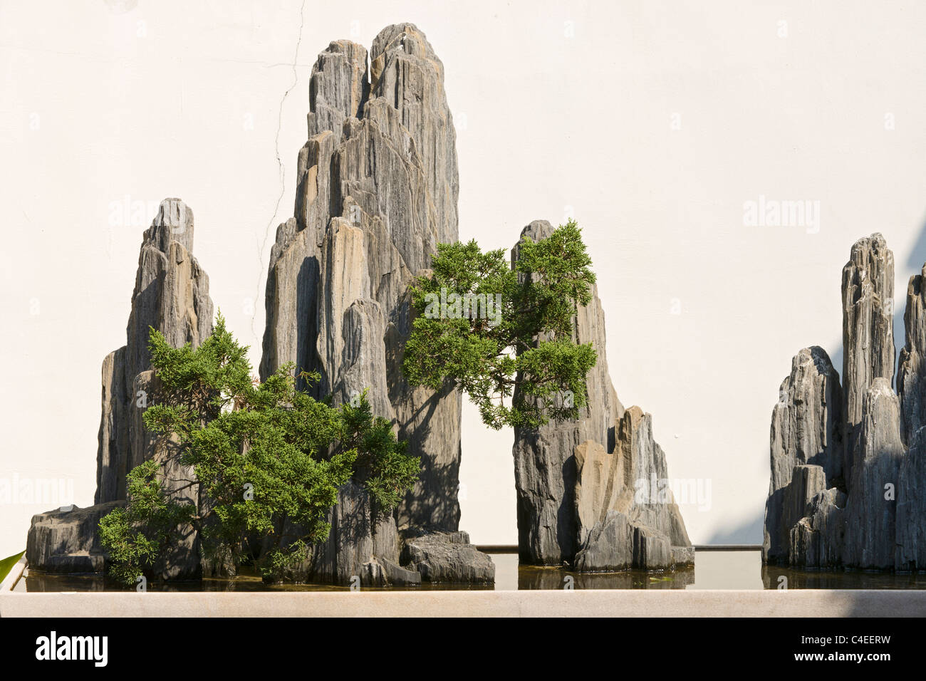 Miniature landscape with rock formations that simulate mountain peaks and accompanied by a suggestion of forest. - Stock Image