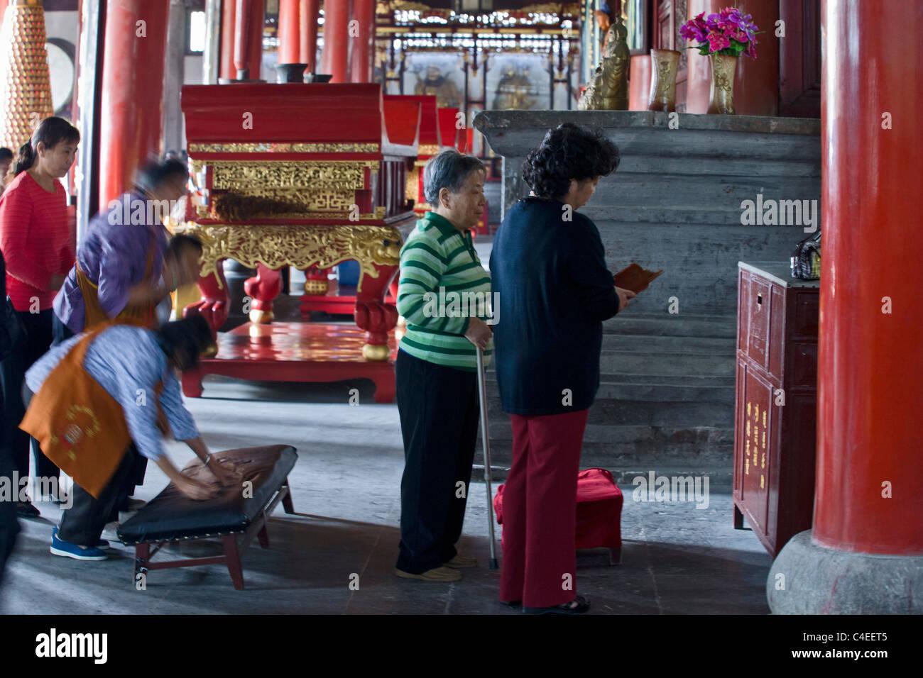 People shaking out fortune sticks at the Taoist temple of Xuen Miao Guan, Suzhou, China. Stock Photo
