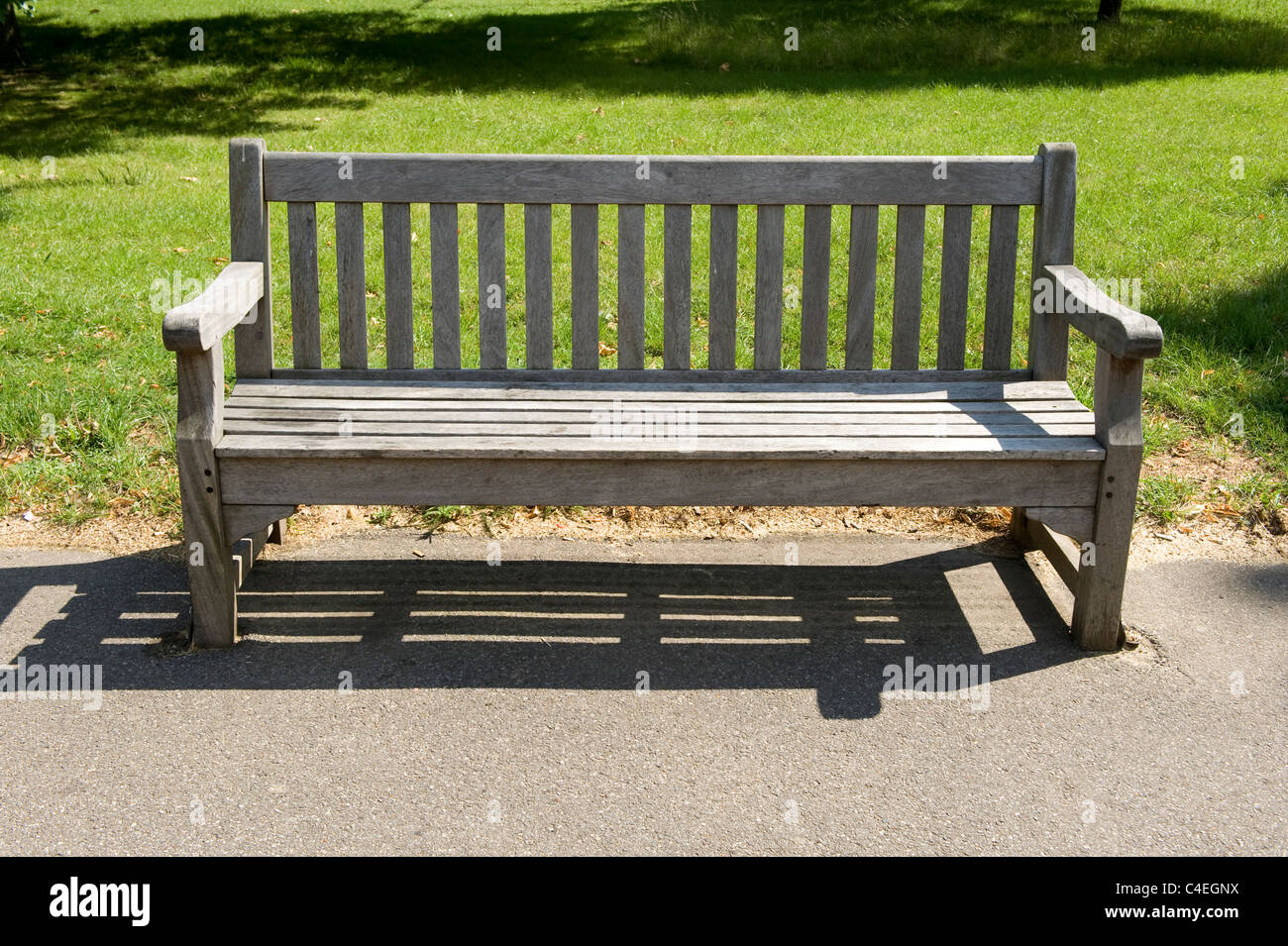 A park bench in a sun-drenched Hyde Park, London. - Stock Image