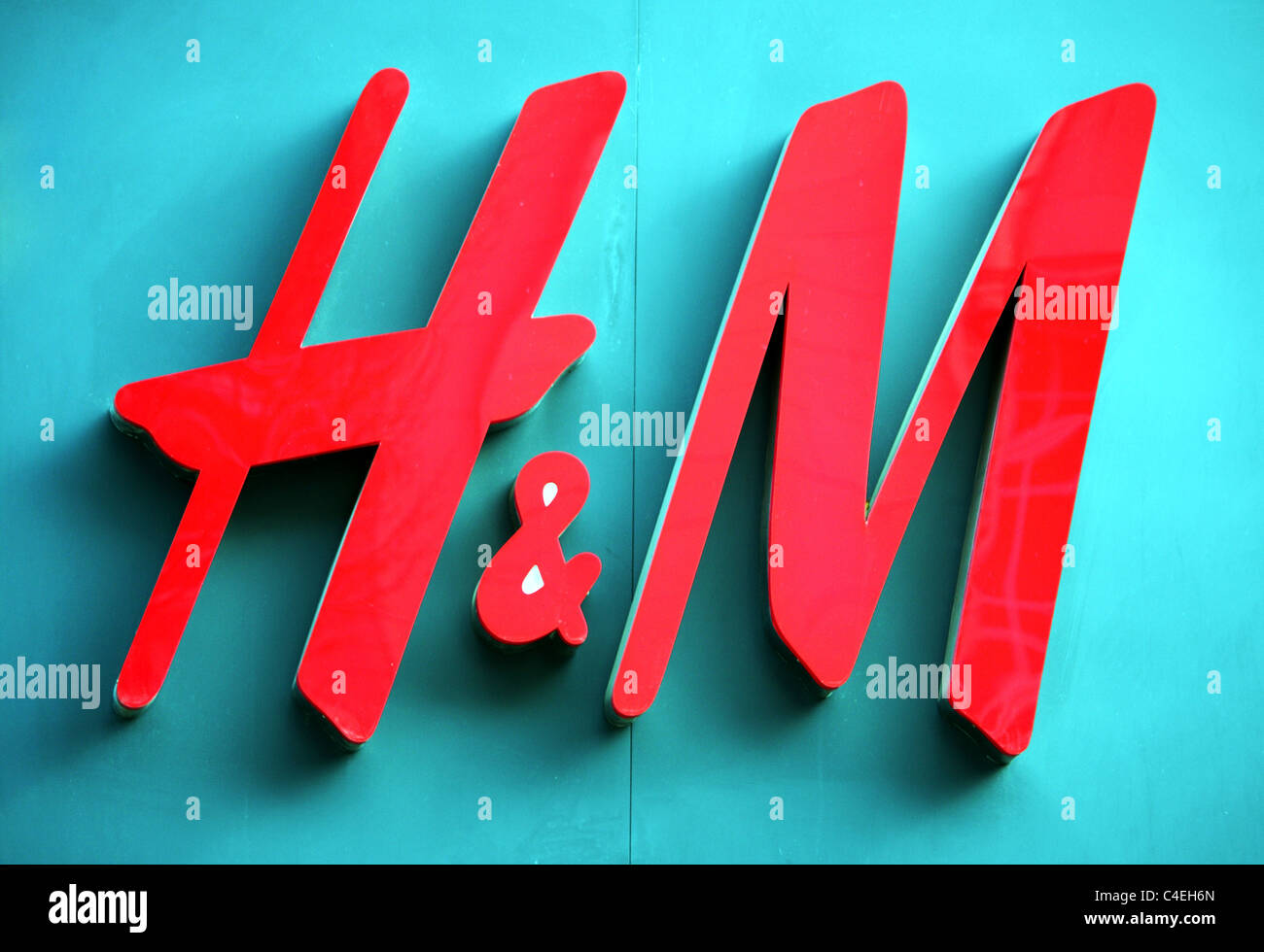 The H&M red 3d logo on the side of a H&M fashion retail shop in England, UK. - Stock Image