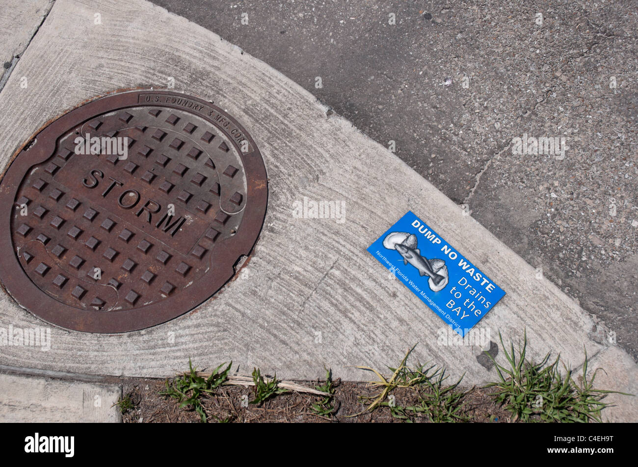 Florida Panhandle Apalachicola storm drainage and sign warning about pollution of the Gulf coastal waters. - Stock Image