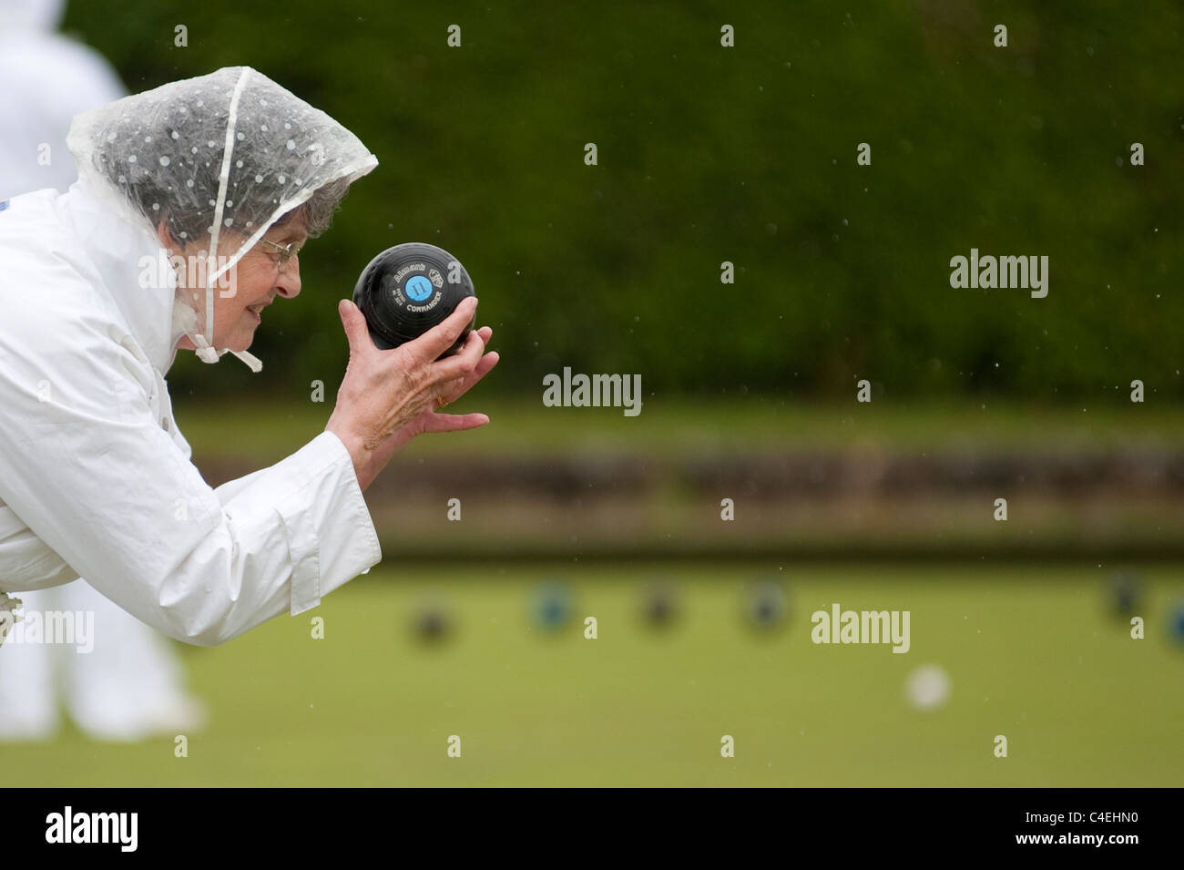 An active female pensioner takes part in a Sunday afternoon Lawn Bowls match in the rain - Stock Image