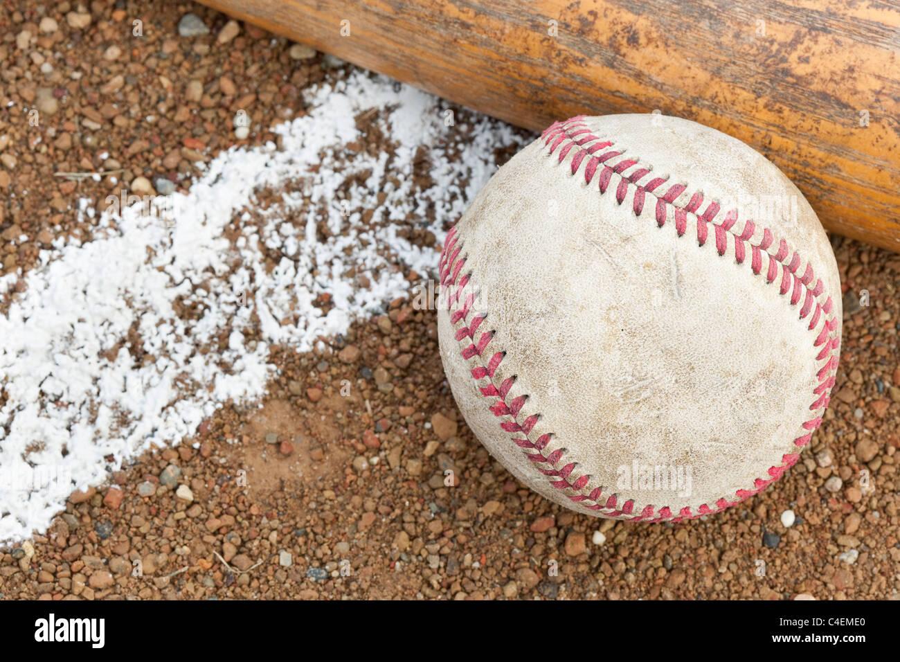 An old worn baseball and bat on a baseball field - Stock Image