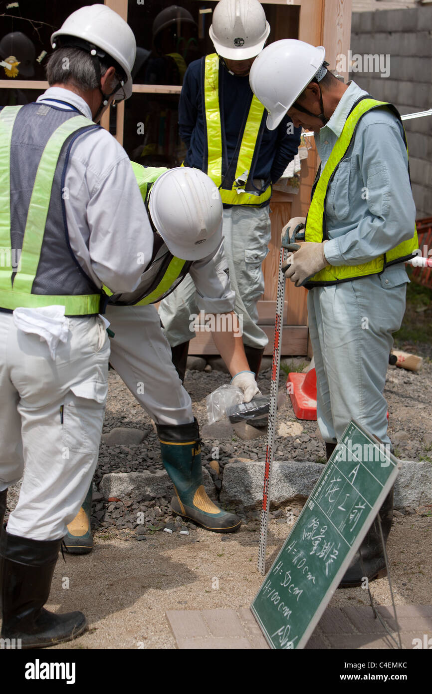 Workers undertake radiation contamination monitoring in the grounds of Children's Nursery, in Fukushima city, - Stock Image