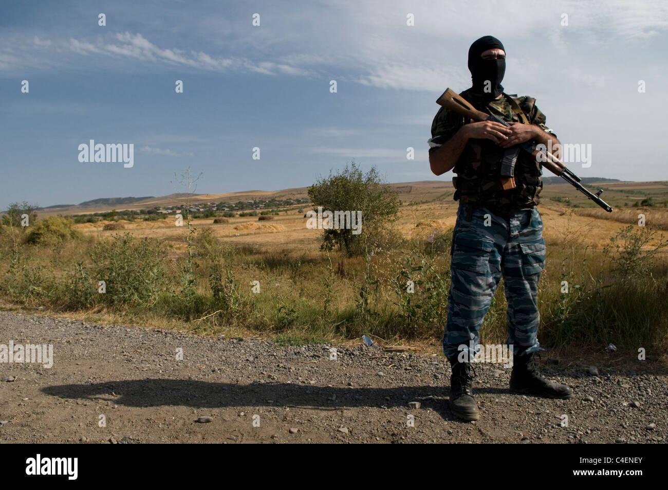 An Abkhaz militia gunman armed with a Kalashnikov AK-47 assault rifle wearing black balaclava near the city of Gori, - Stock Image
