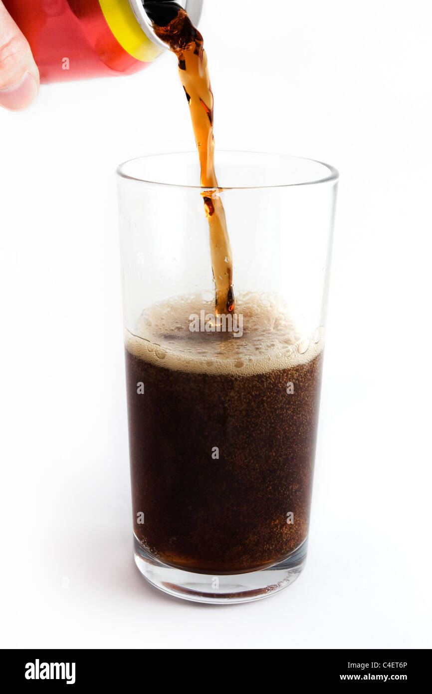 Cola drink pouring into a glass from the can over white - Stock Image