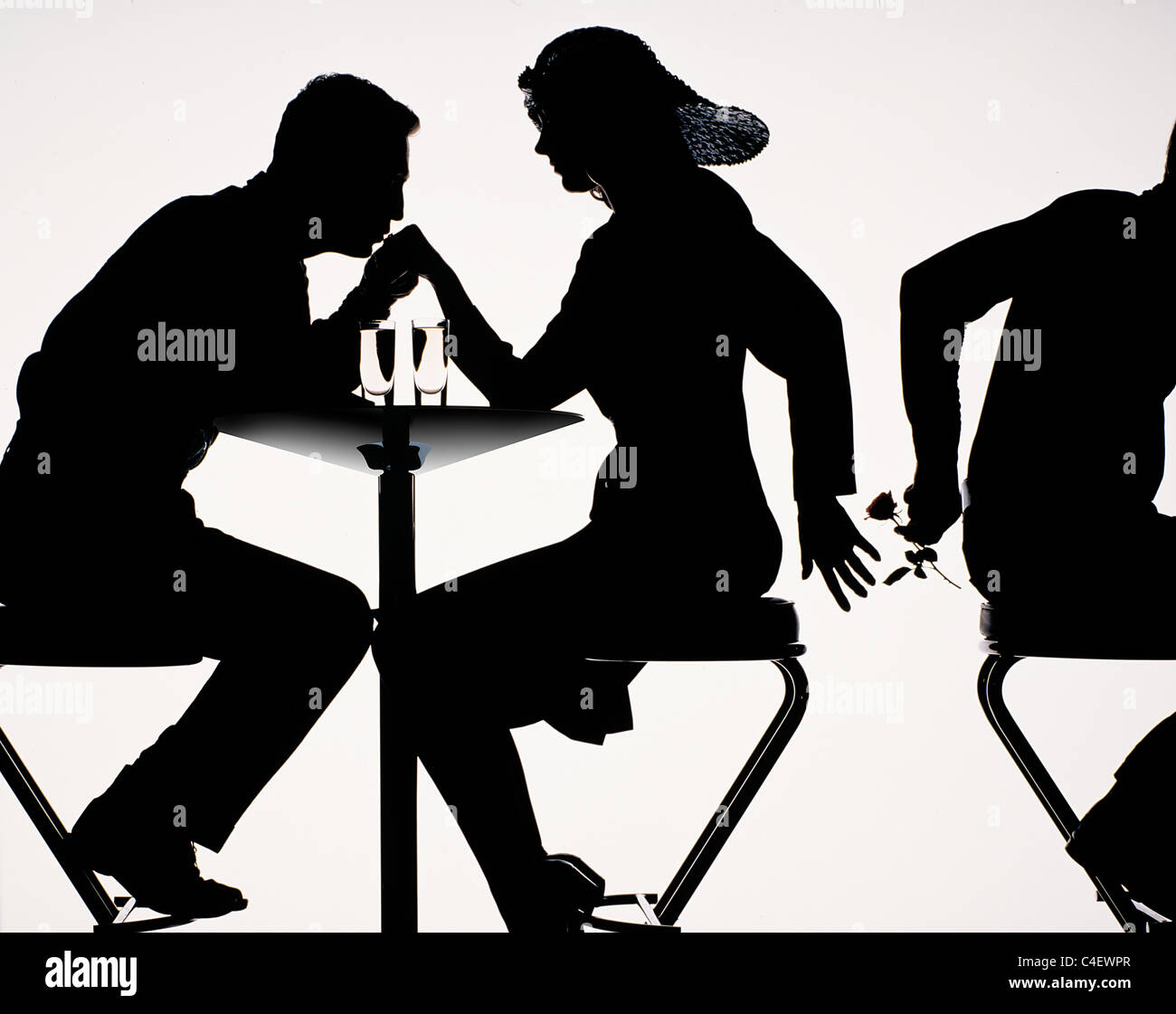 Infidelity. Silhouette of couple sitting on bar stools at high table with drinks, and a rose being passed to the - Stock Image
