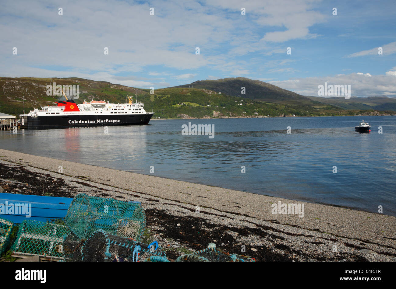 The Caledonian MacBrayne ferry at Ullapool with mountains behind and fishing pots in the foreground - Stock Image