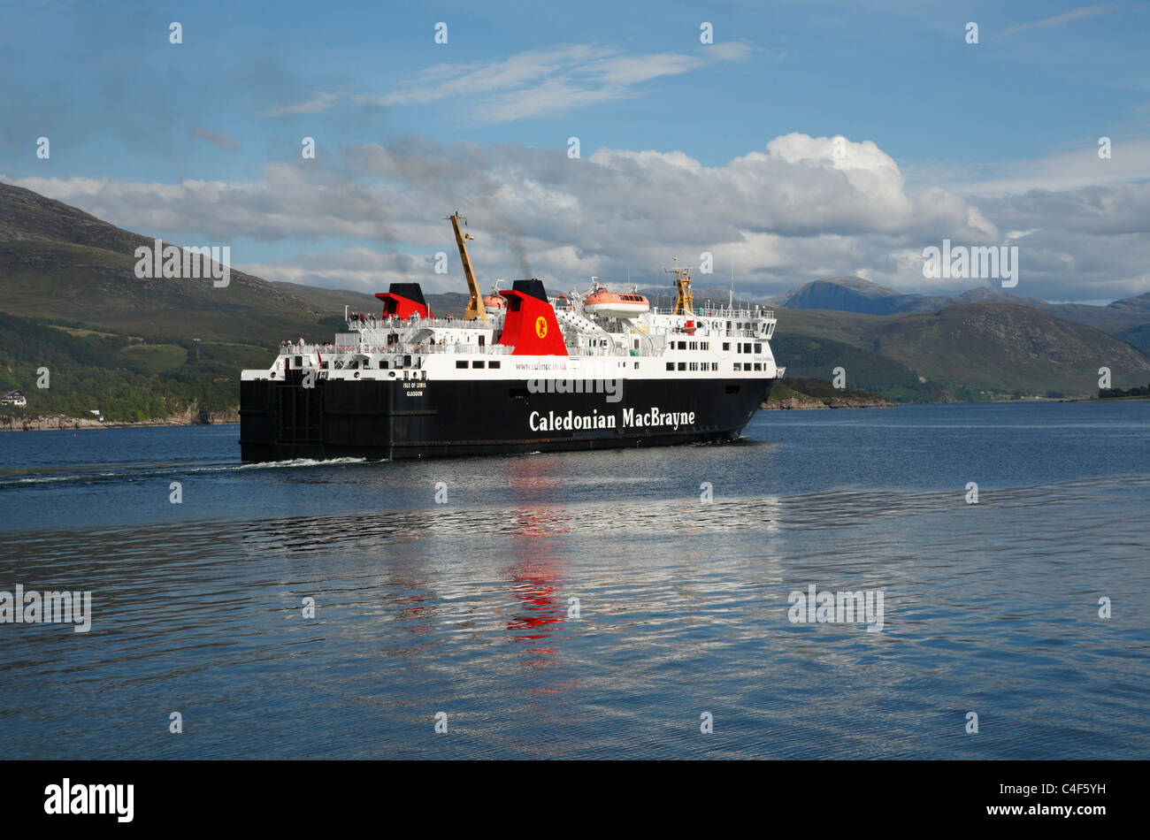 The Caledonian MacBrayne ferry at Ullapool  setting sail with mountains behind. - Stock Image