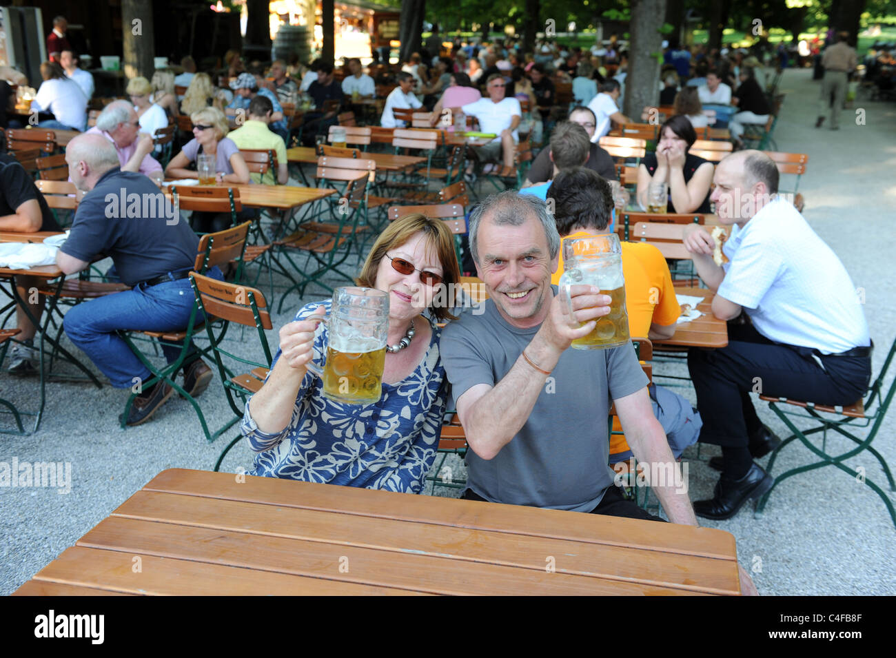 Tourists drinking beer at The Hirschgarten the largest beer garden in Munich - Stock Image