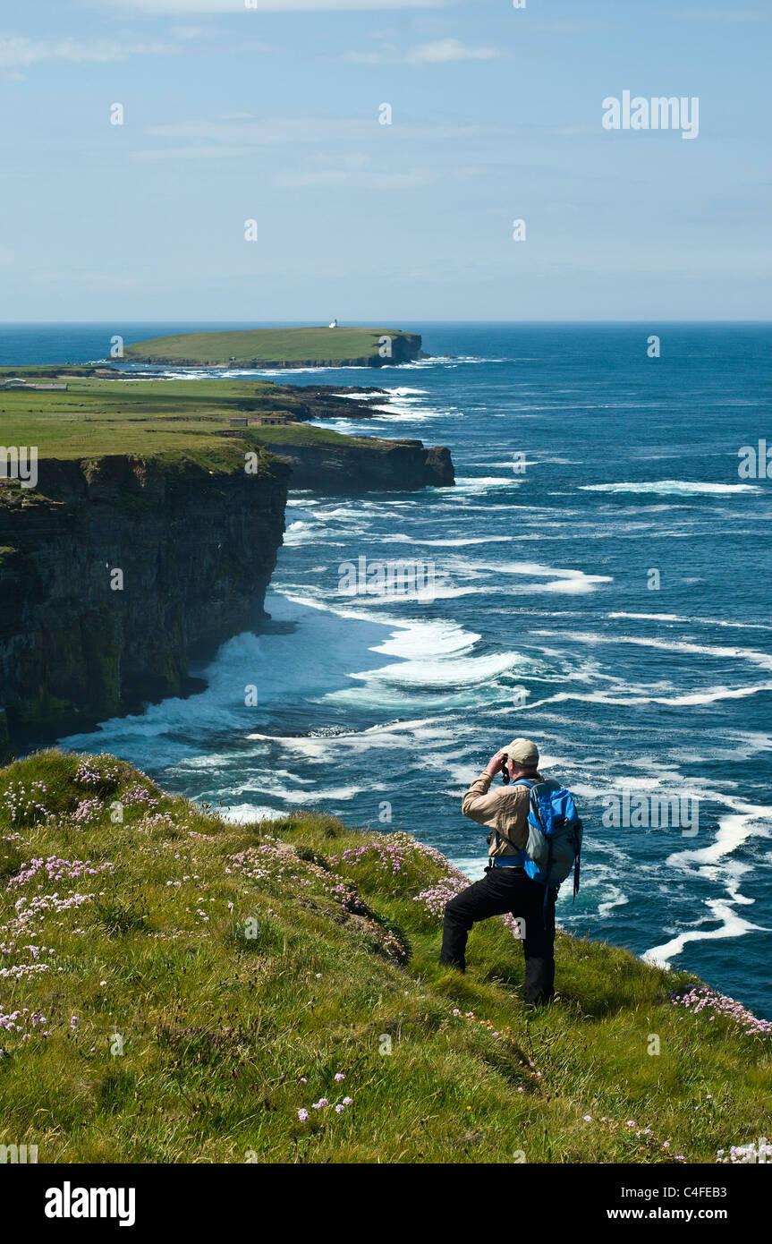 dh North coast BIRSAY ORKNEY Seacliffs birdwatcher with binoculars watching bird watcher scotland cliff uk Stock Photo