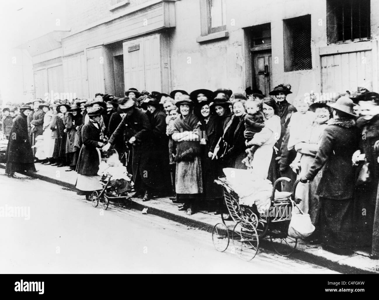 Women and children wait in a bread line in wartime England. - Stock Image