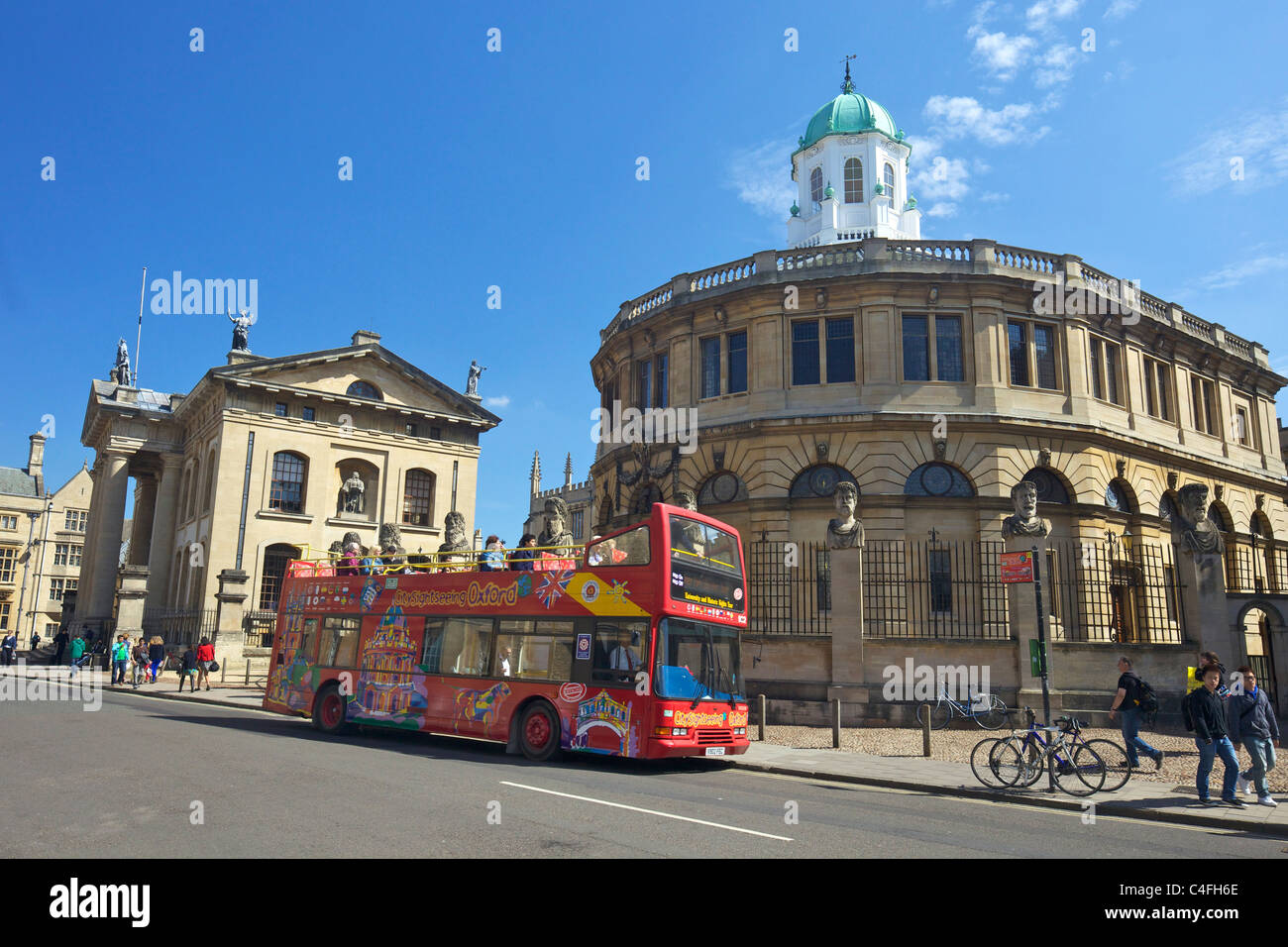 Open-top tourist bus outside Sheldonian Theatre and Clarendon Building, Broad Street, Oxford University, City centre, - Stock Image