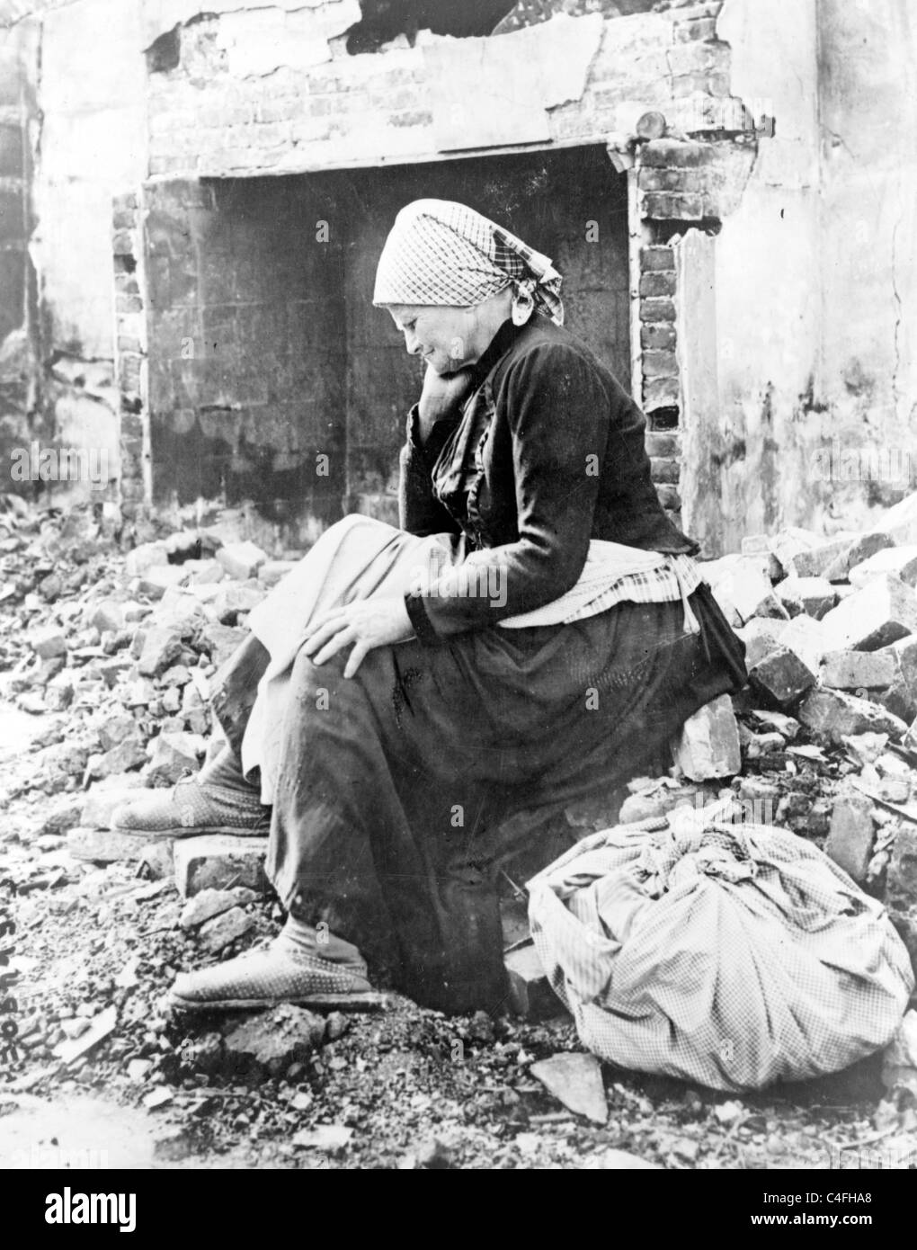 French woman returns to her wartime home to find it in ruins. Elderly woman seated at ruins of her home in the Somme - Stock Image