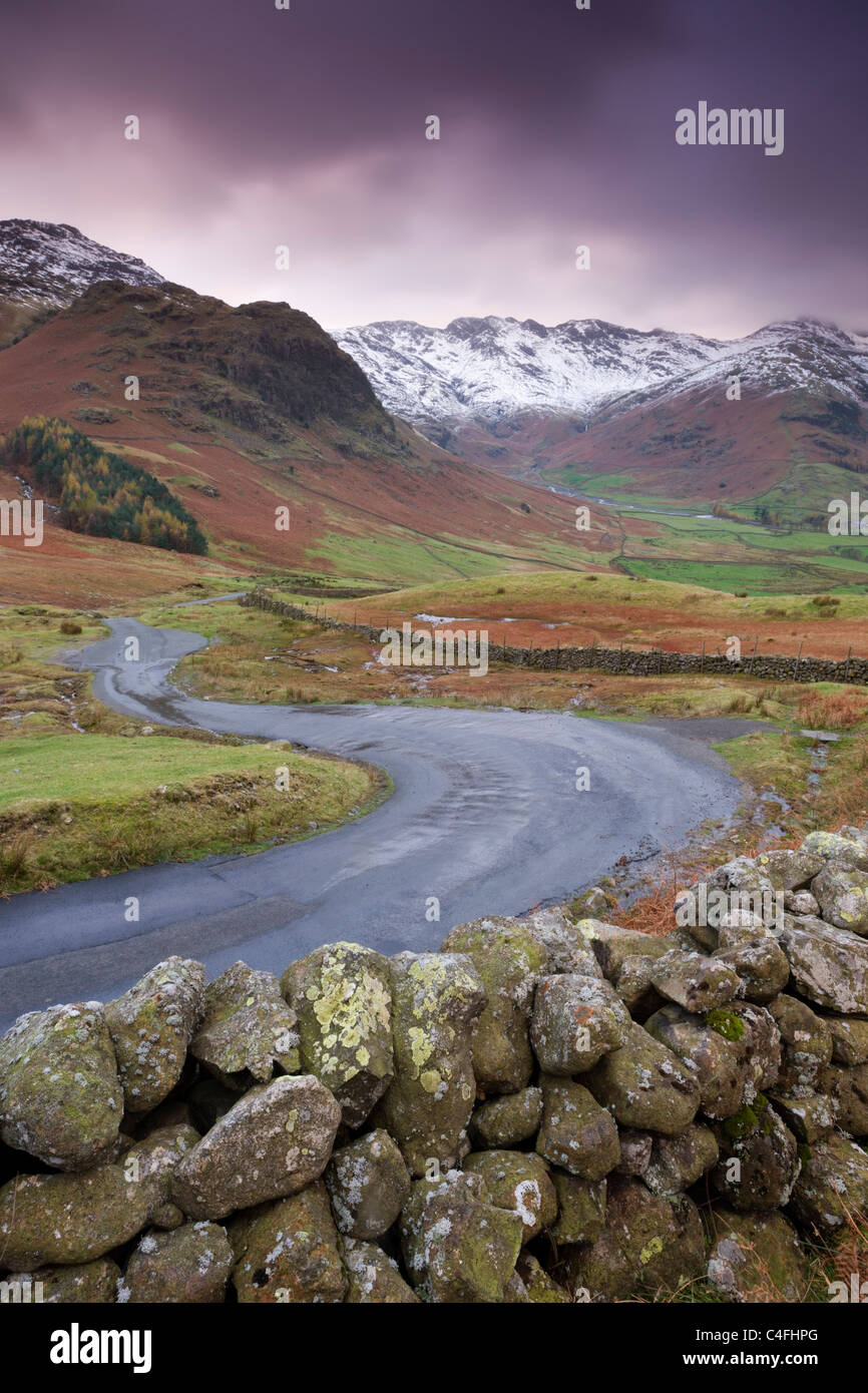 A winding mountain road descends into Great Langdale valley, Lake District National Park, Cumbria, England. - Stock Image