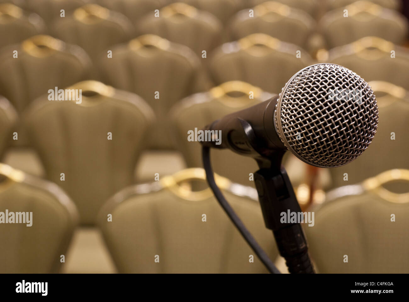 Microphone in front of several rows of empty chairs with shallow depth of field - Stock Image