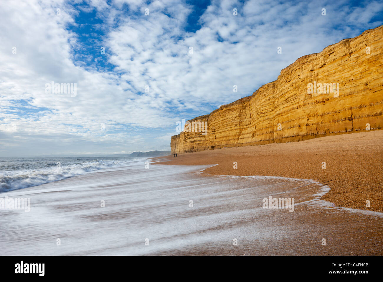 Waves wash clean Hive Beach backed by towering sandstone cliffs, Burton Bradstock, Dorset, England. Winter (February) - Stock Image