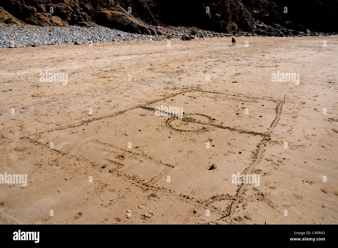 A miniature football pitch marked out on a beach - Stock Image