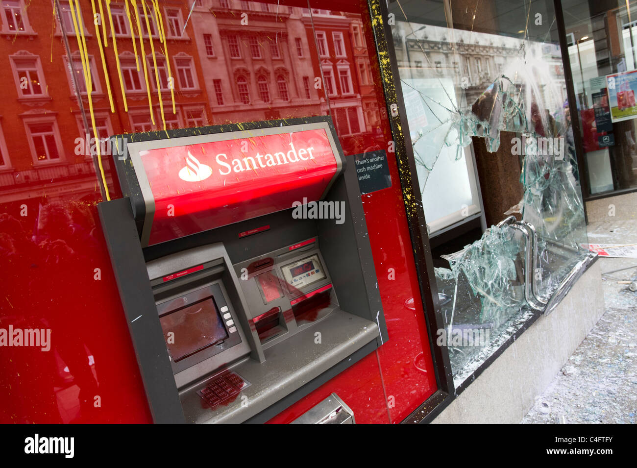 Vandalised bank ATM and smashed window broken by anti capitalists protesters, London, UK - Stock Image