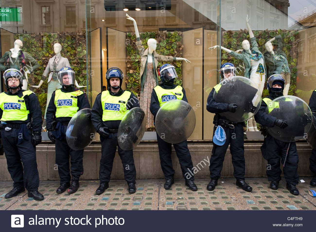 Line of riot police protecting shop during protest march, London, UK - Stock Image