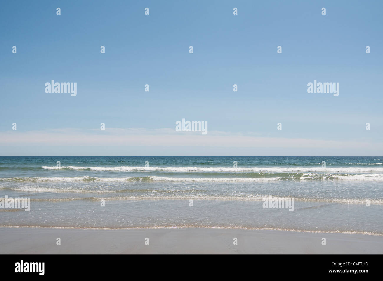Waves wash ashore the sandy beach in Ogunquit, Maine, USA. - Stock Image