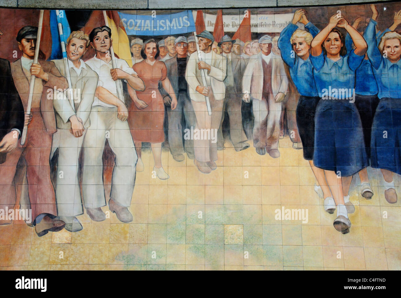 Socialist wall mural of happy workers on the wall of the Ministry of Finance building in ex East Berlin - Stock Image