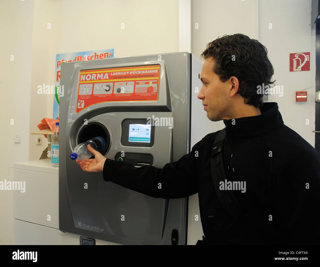 A man putting a plastic bottle in a bottle recycling machine in German supermarket - Stock Image