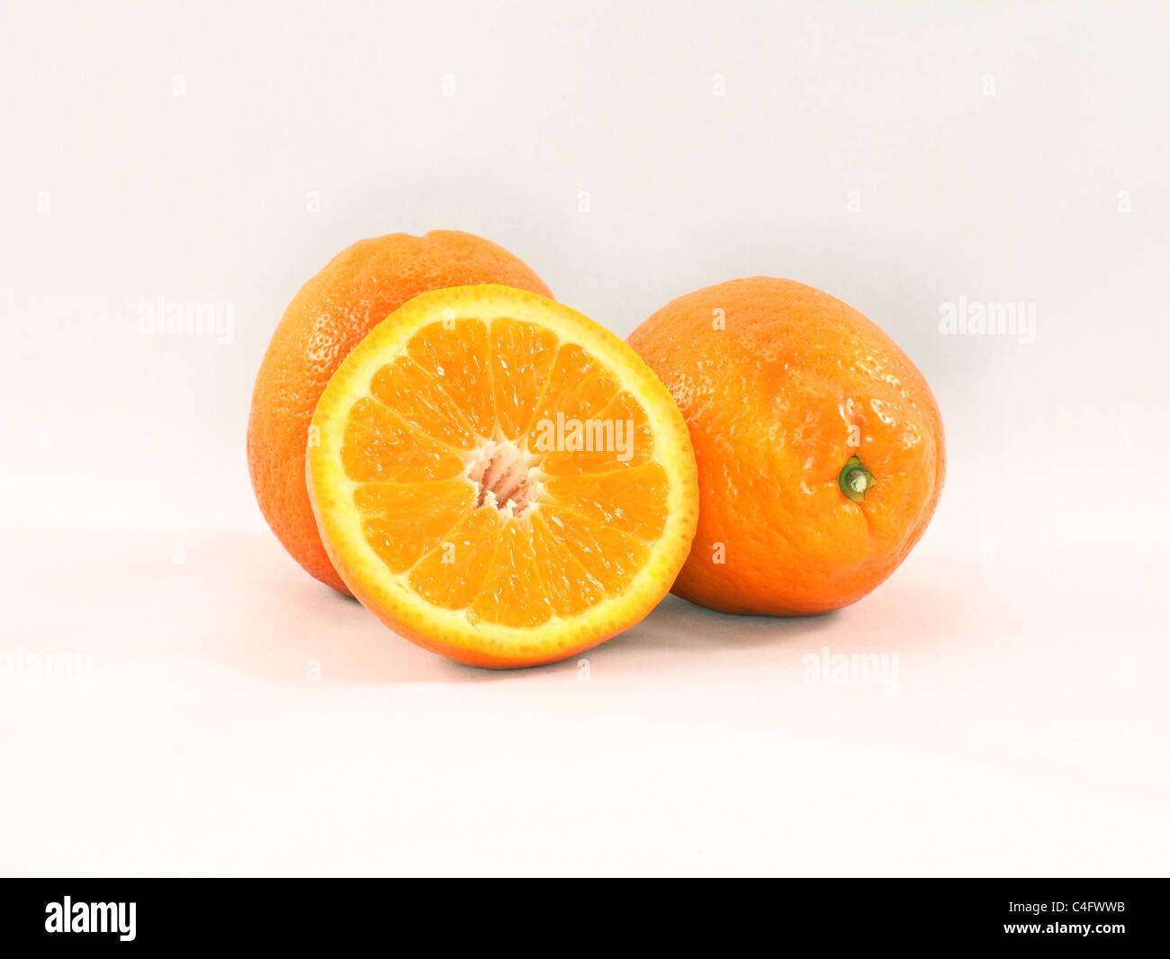 Three ripe Minneola tangelo oranges, one sliced in half. - Stock Image