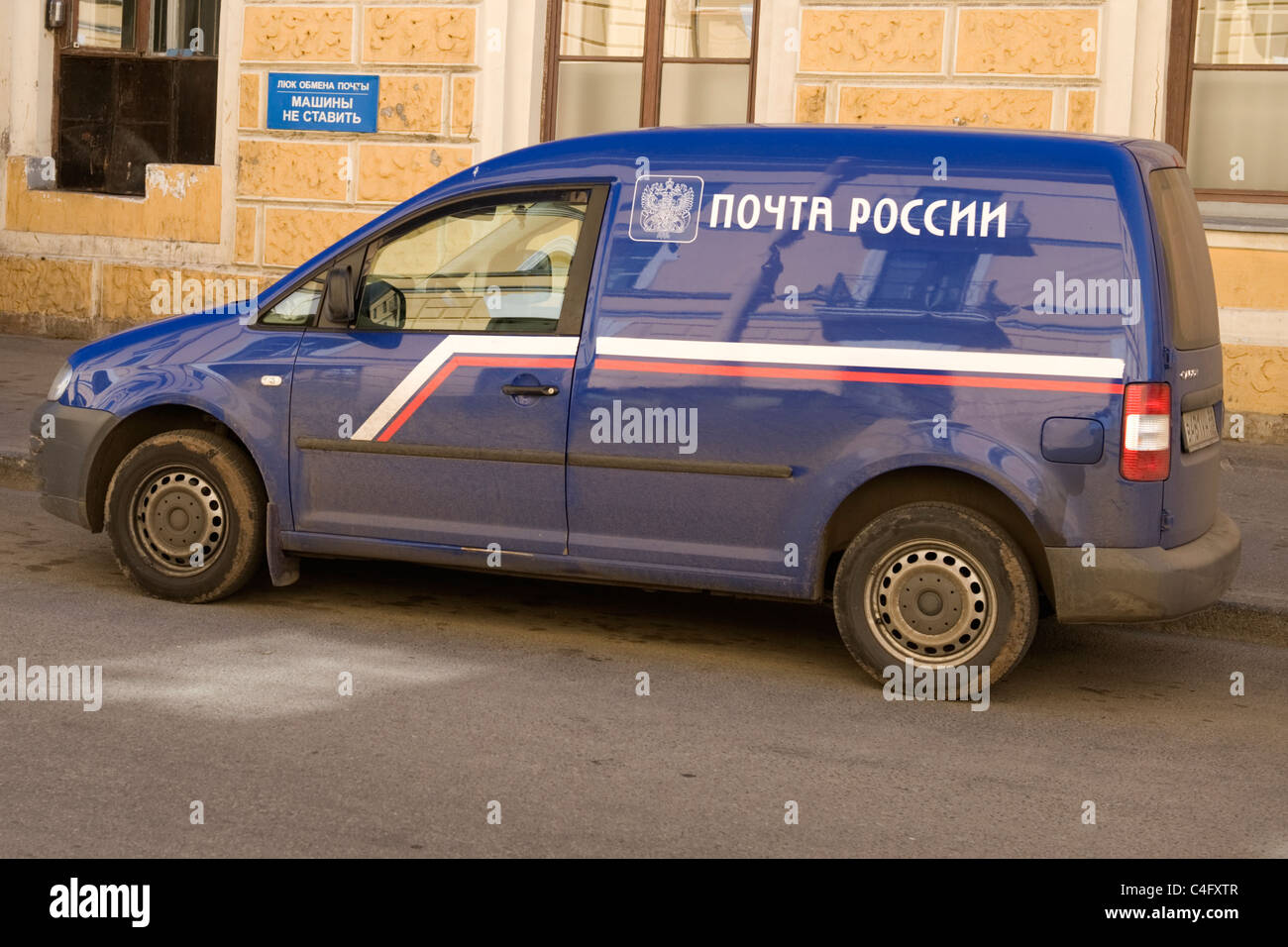 Russia St Petersburg Russian Postal Service dark blue dirty van parked outside main post office street scene - Stock Image
