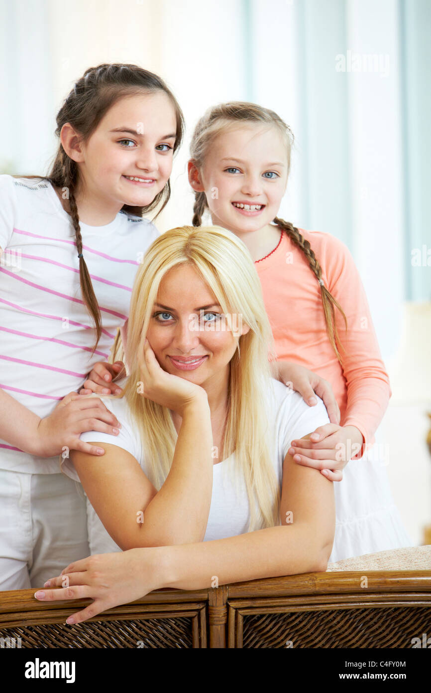 Portrait of happy mother being embraced by two daughters while looking at camera Stock Photo