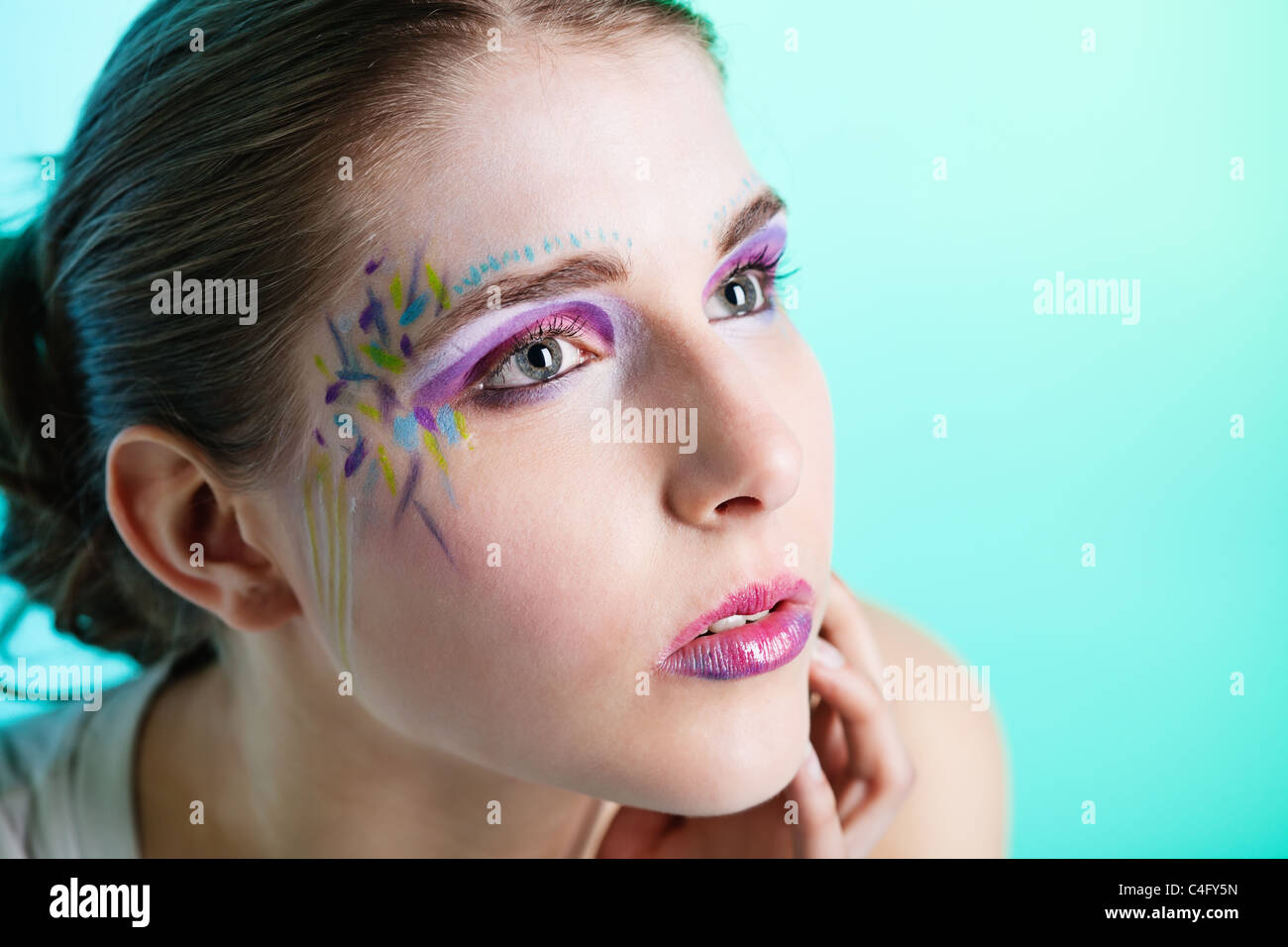 Closeup portrait of a pretty young woman with face art - Stock Image