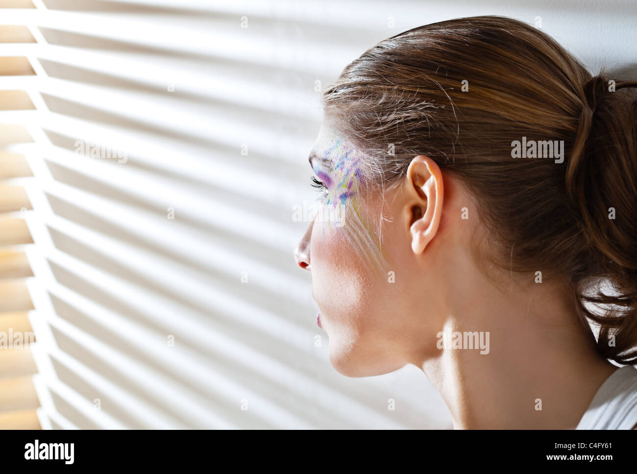 Pretty young woman lean lit by bright sunlight coming through the blinds - Stock Image