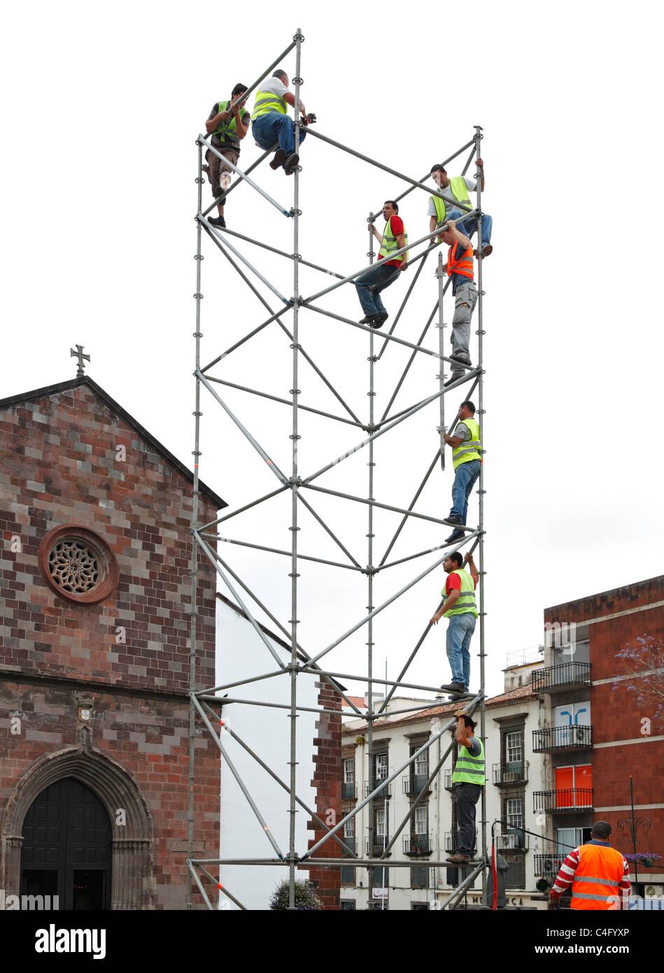 Team of men erecting scaffolding. - Stock Image