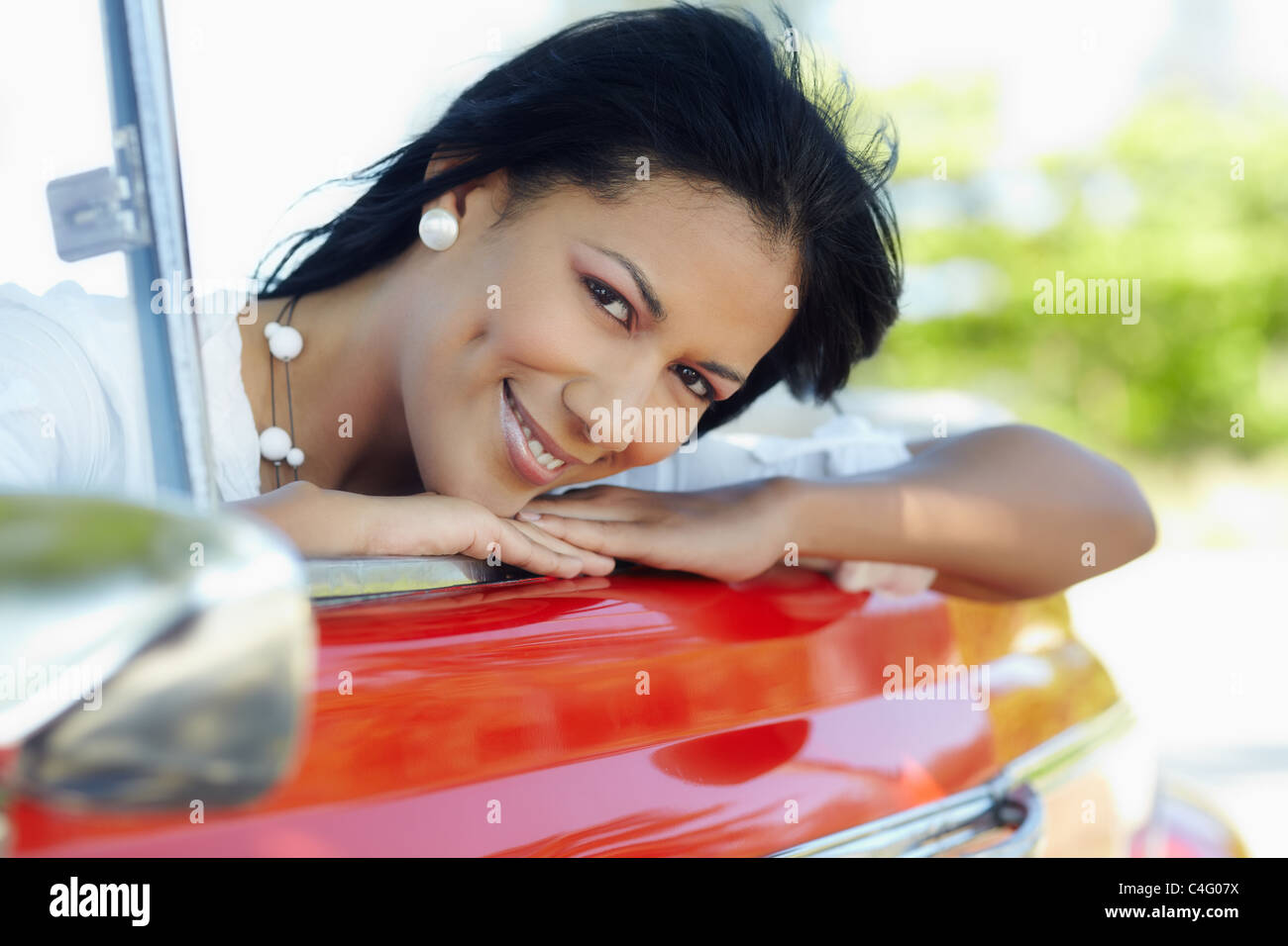 young adult brunette woman leaning on convertible red car and looking at camera. Horizontal shape, side view - Stock Image