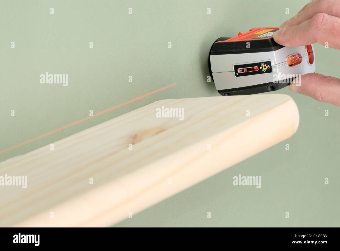 Using a laser spirit level  to check shelf alignment - Stock Image